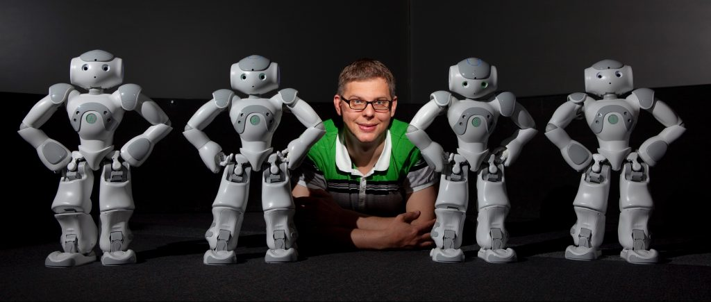 Academic staff member Dr. Christoph Bartneck with four Nao robots from Aldebaran.